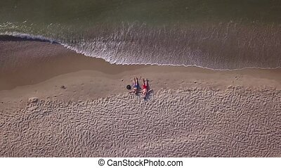 Couple lying down on beach aerial top view drone shot at sea beach