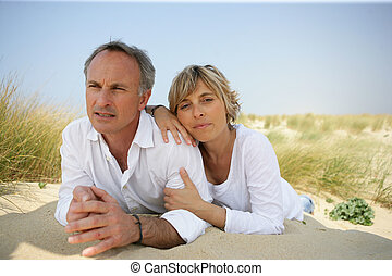 Couple lying in a sand dune