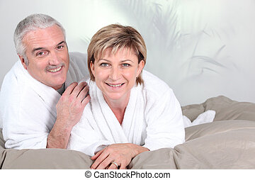 Couple lying in bed after a shower