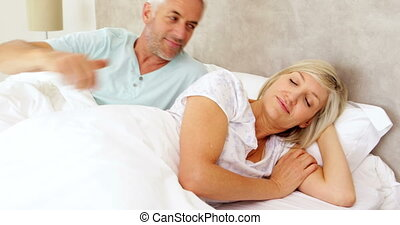 Couple lying in bed and smiling