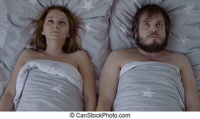 Embarrassed Couple is going to have Sex, but are Shy and do not know what to do. Top view of bearded Man and Woman for the first time together in Bed.