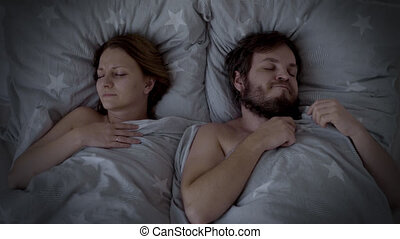 Man Snoring in Bed, Woman cannot sleep. Husband snoring, his Wife is Waking up and closing her ears. Spouses are Sleeping in bedroom at Night.