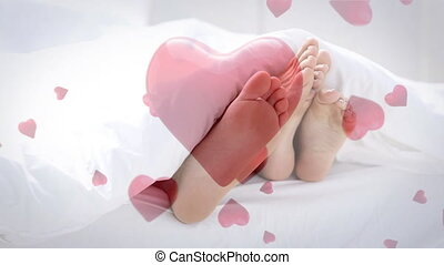 Couple lying in bed playing with feet