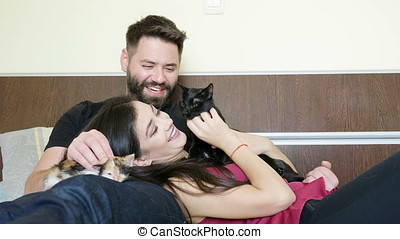 Couple lying in bed with their cats in arms