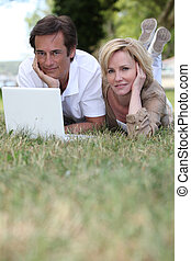 couple lying in grass using laptop