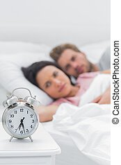 Couple lying in their bed next to an alarm clock