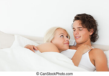 Couple lying on a bed hugging