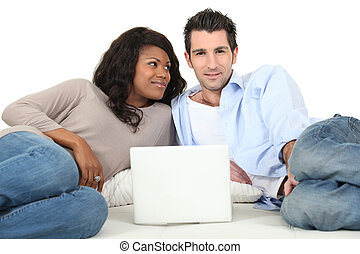 Couple lying on a bed looking at a laptop