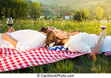 Couple lying on a picnic blanket with glass of wine