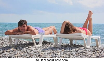 couple lying on beach beds in pebble beach, sea and clouds in background