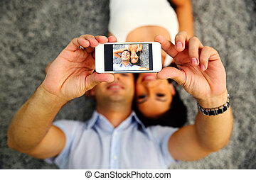 Couple lying on the carpet and making selfie photo on...