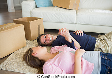 Couple lying on the floor with their moving boxes