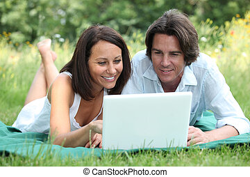 Couple lying on the grass looking at a laptop computer screen