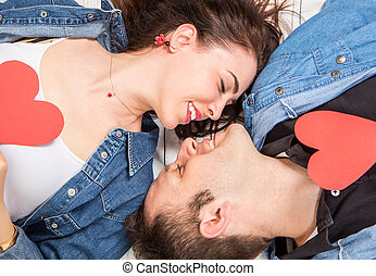 Couple lying on the wooden floor with hearts