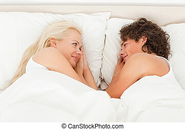 Couple lying while looking at each other