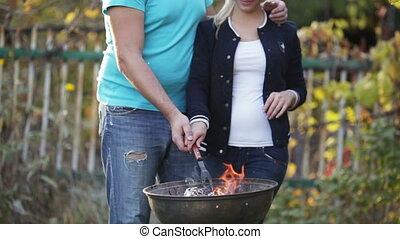 Couple make fire in barbecue