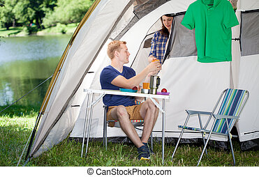 Couple making breakfast in front of tent