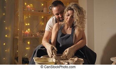 Couple making clay jug on the wheel.