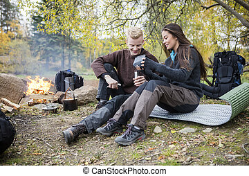 Couple Making Coffee On Campsite In Forest