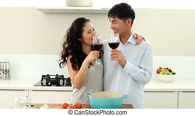 Couple making dinner and drinking r