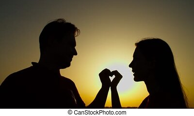 Couple making heart shape with arms at sunset - Silhouette ...
