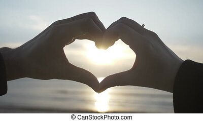 Couple making heart shape with their hands with sunset inside on the beach in slow motion