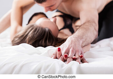 Couple making love in bedroom - Horizontal view of couple...