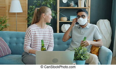 Couple making online video call from home talking clinking ...