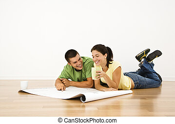 Couple making plans. - Attractive young adult couple lying...