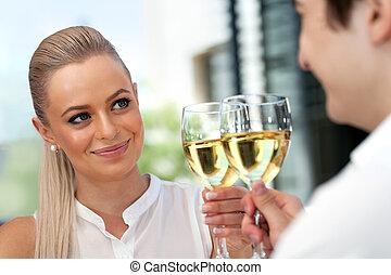 Couple making romantic toast on date.