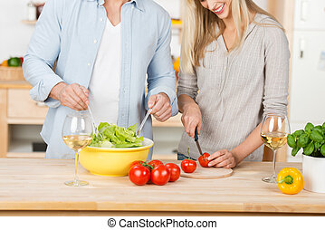 Couple Making Salad Together At Kitchen Counter