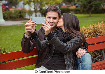 Couple making selfie photo on the bench outdoors