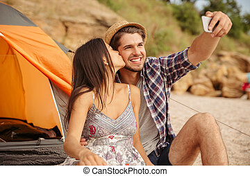 Couple making selfie with smartphone and having fun camping