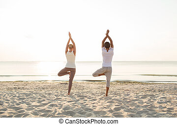 couple making yoga exercises outdoors from back - fitness,...