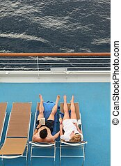 couple: man and woman both relaxing on chaise longues.