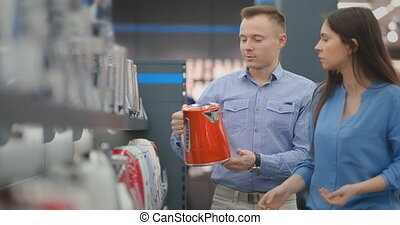 Couple man and woman choose electric kettle in the store.