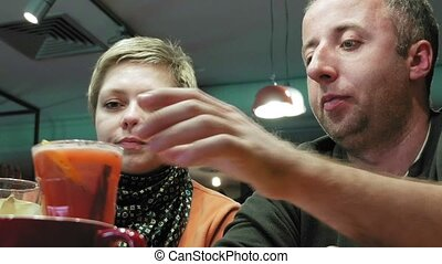 Couple man and woman clink glasses eats and talks in cafe...