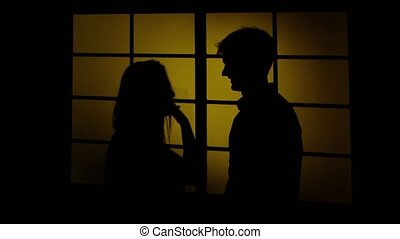 Couple man and woman fighting. Silhouette. Close up