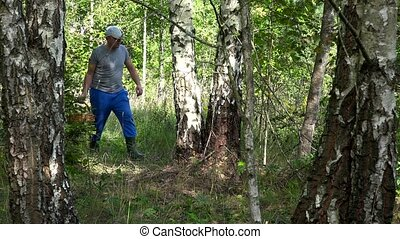 Couple man and woman walking with baskets full of mushrooms in forest