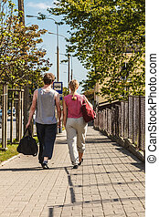 Couple man and woman walking with sport bags.