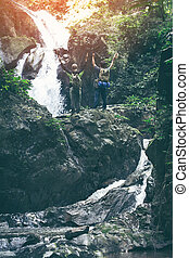 Couple man with waterfall hidden in the tropical jungle