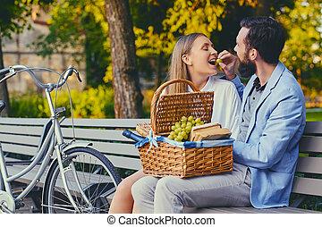 couple, mange, raisin, sur, a, banc, dans, a, park.