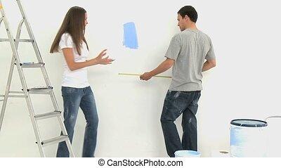 Couple measuring a wall