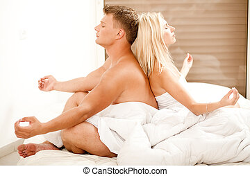 Couple meditating - Young man and woman meditating in bed