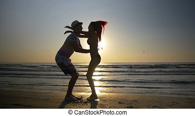 Couple meeting and kissing on shore and woman jumps in her lover arms in slow motion
