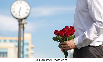 Couple meeting on a date, young man giving red rose to his beautiful girlfriend