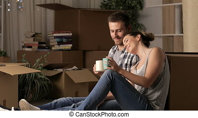Couple moving home resting drinking coffee sitting on the...
