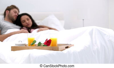 Couple napping after breakfast in bed at home with tray on...