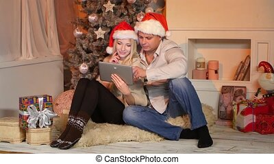 Couple near christmas tree in christmas decorated house with tablet pc