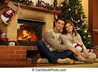 Couple near fireplace in Christmas decorated house interior